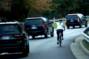 Woman flips off Trump after pursuing his motorcade on bicycle