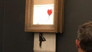 Banksy artwork self-destructs moments after it is sold for $1.4 million (bbc.com)